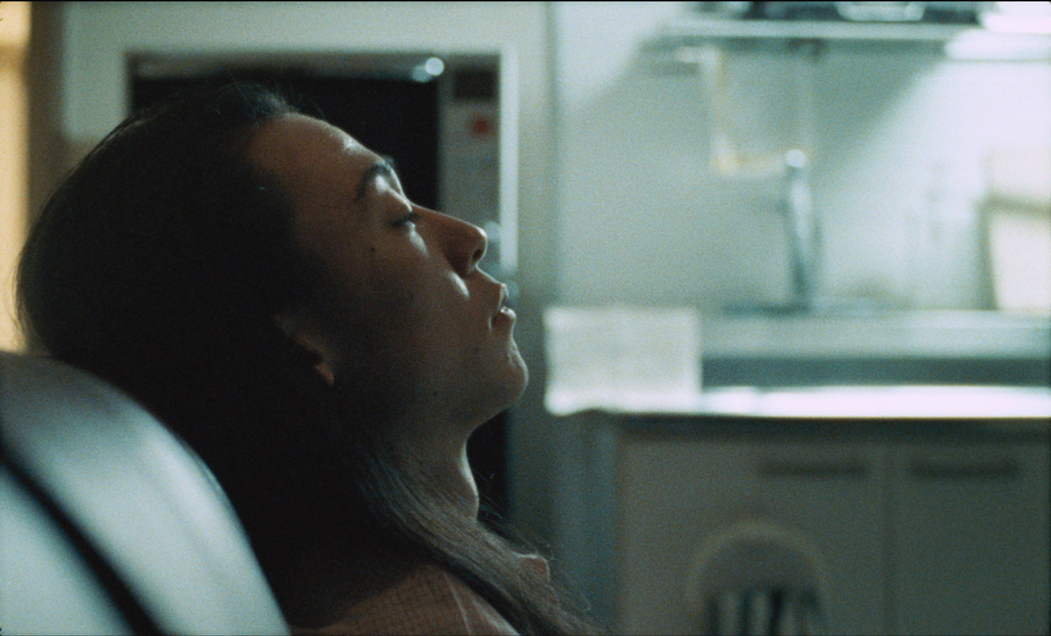 Image of a woman sleeping, a still from Ane Hjort Guttu and Daisuke Kosugi's video work, entitled The Lost Dreams of Naoki Hayakawa, dated 2016