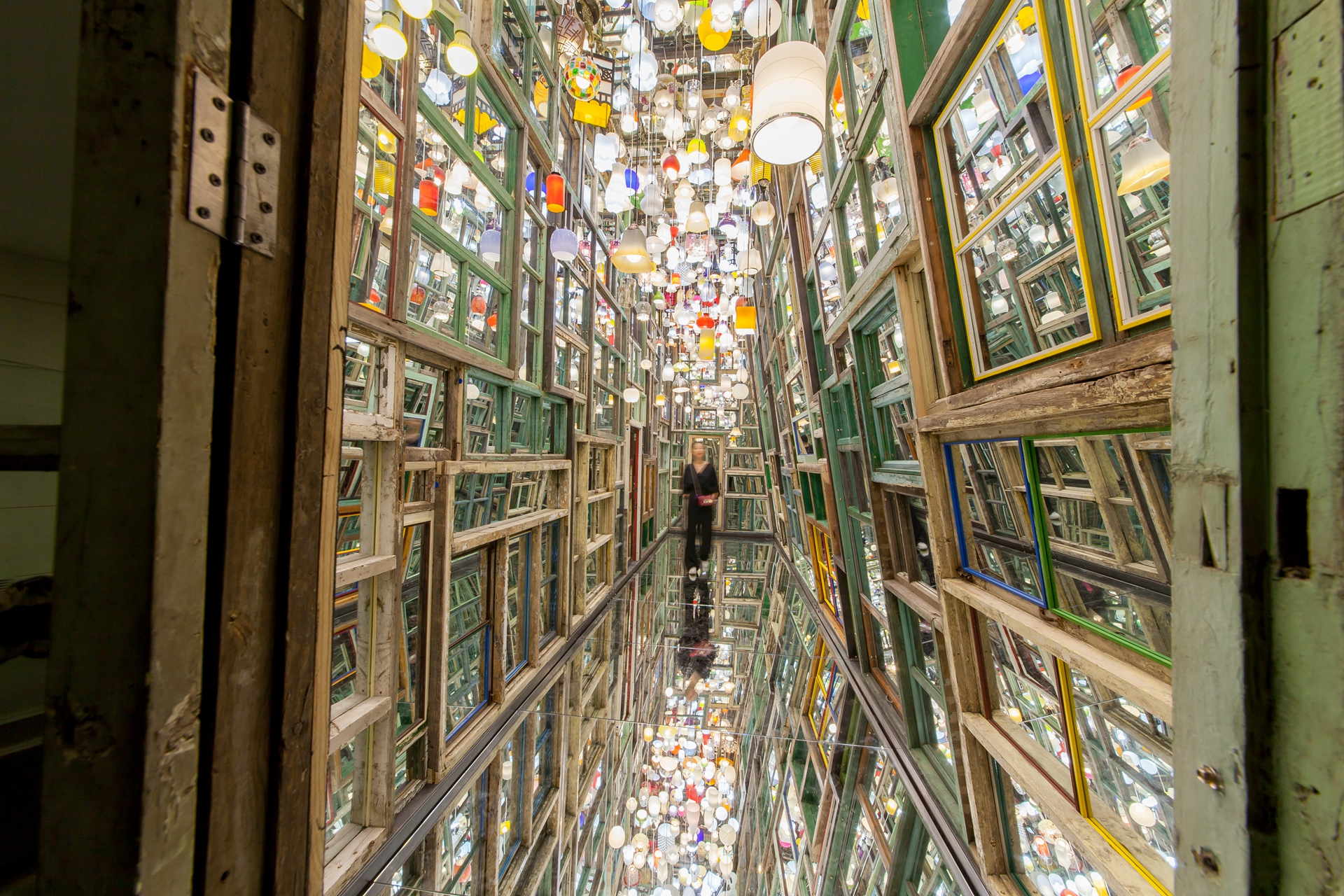 An installation of mirrors forming a reflective hallway by artist Song Dong