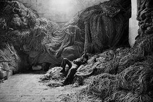 A tuna fisherman asleep on a net, Trapani, Sicily, Italy by Sebastião Salgado contemporary artwork