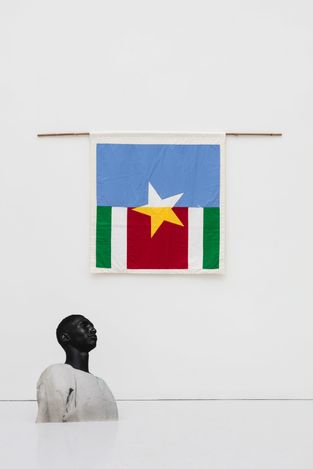 Samson Kambalu,The Country Drowning in Unhealthy NationalismandKeyala Soldier (2019). Cotton and silk flag, bamboo, black and white photo on board. Courtesy the artist and Kate MacGarry, London.
