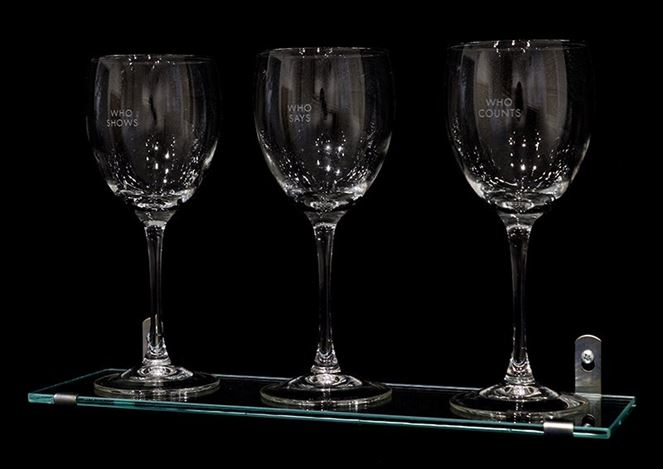 Louise Lawler,                                         Who Says, Who Shows, Who Counts (1990).                                        Set of 3 etching glasses with glass shelf & metal wall attachments.                                         Edition of 50. Glasses: 8 x 3 inches each  (20.3 x 7.6 cm each) Glass shelf: 14 x 4 1/2 inches  (35.6 x 11.4 cm) Signed and numbered on accompanying certificate. Courtesy Krakow Witkin Gallery.