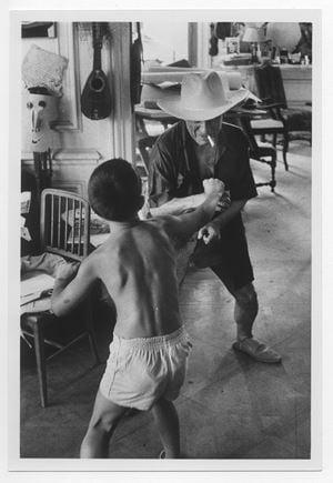 Bataille entre Claude et son père portant le chapeau de cow-boy de Gary Cooper [Battle between Claude and his father wearing Gary Cooper's cowboy hat] by David Douglas Duncan contemporary artwork