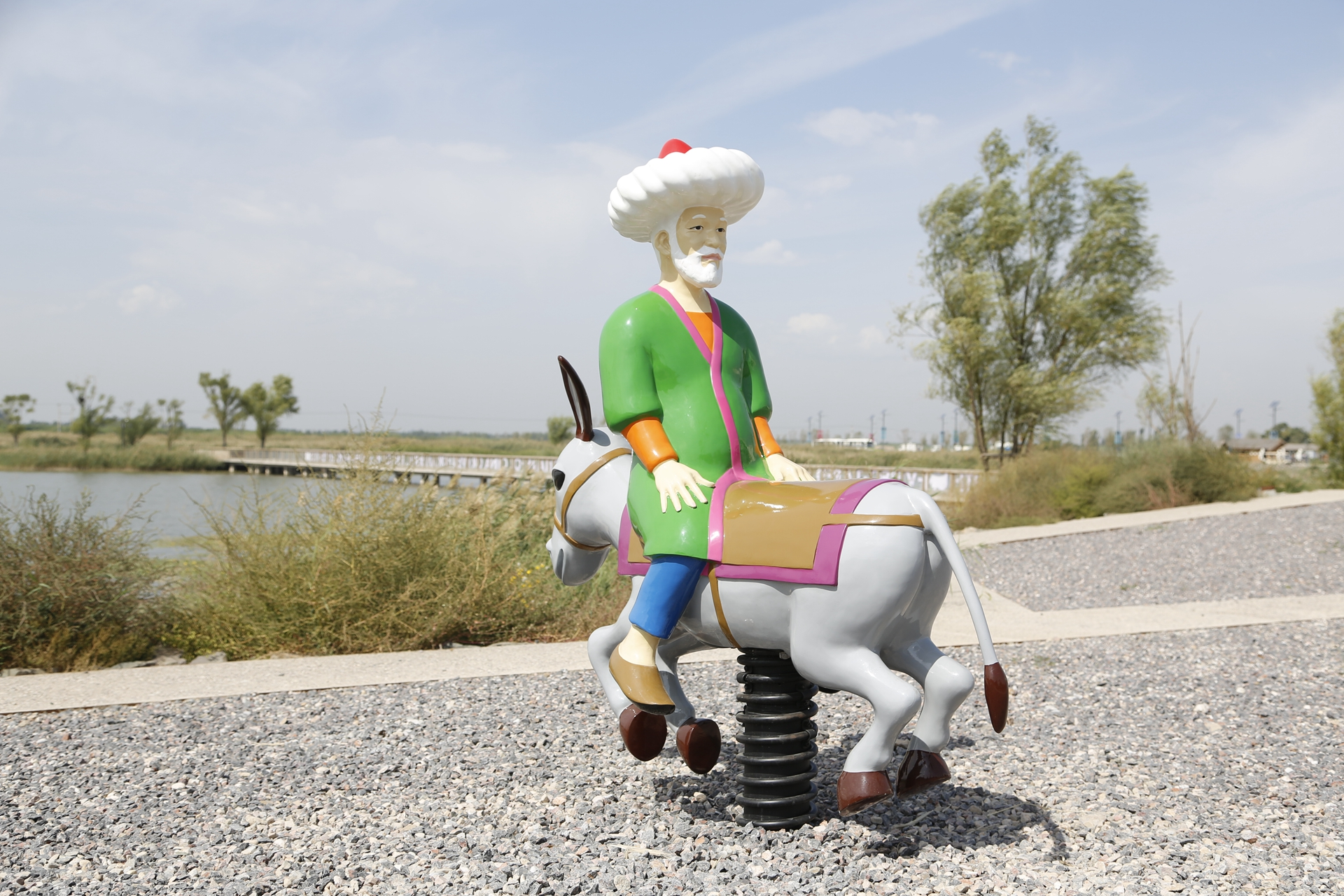 A sculpture by artist duo Slavs and Tatars resembling a children's playground's spring rider of an old man riding a donkey backwards