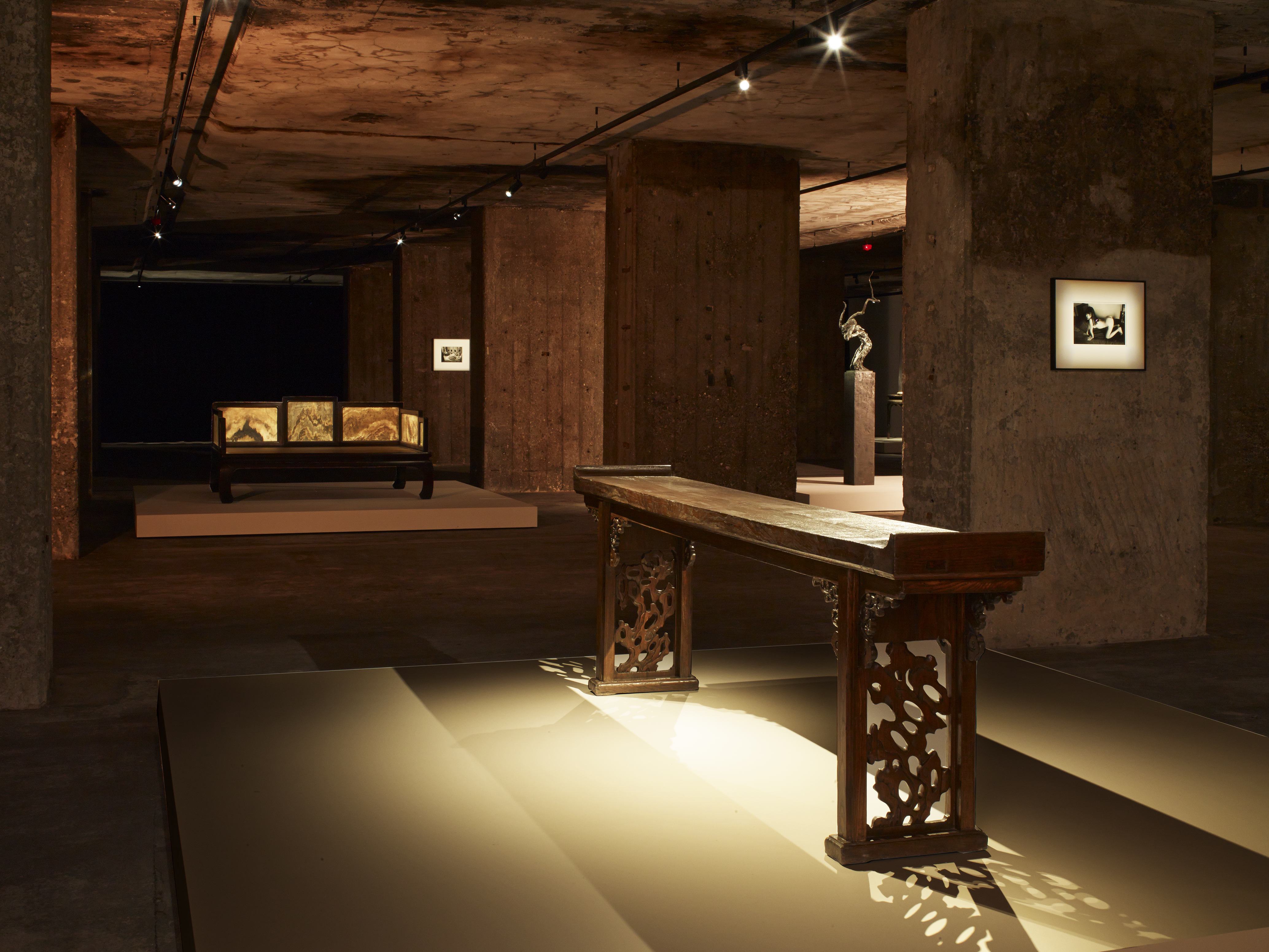 Image: Exhibition view of The Feuerle Collection, Side table with everted ends, Early Qing dynasty, 17th Century. Elm, Approx. 272 cm long. In the the background: Lohan Bed, Qing Dynasty, 17 Jichi wood. Approx. 149 x 204 x 100cm. Zeng Fanzhi, Untitled, 2009. 117 x 61 x 42 cm. bronze, 129.5 x 26 x 26cm (base) and work by Nobuyoshi Araki. Photo: Nic Tenwiggenhorn / VG Bild-Kunst, Bonn. © The Feuerle Collection.