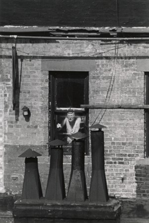 Woman at window with chimneys by André Kertész contemporary artwork