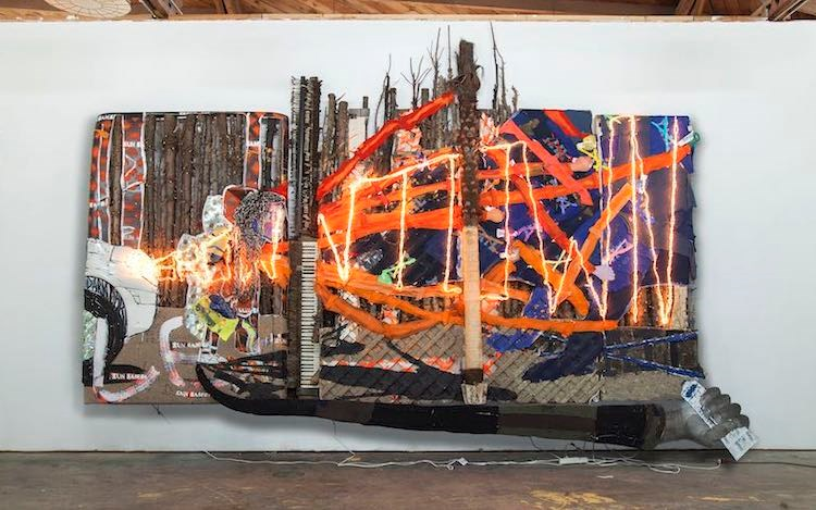 Aaron Fowler,Lex Brown Town(2017). Acrylic, enamel, dirt, tire, car parts, hair weave, wood, artificial palm tree, pianos, fabric, paint tubes, backpack, graduation cap, CDs, LED rope lights, and Plexiglas on wood panels and truck topper. 144 x 192 x 36 inches. Courtesy David Zwirner.