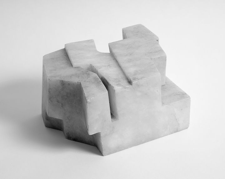 A curved, geometric alabastro sculpture is photographed in black and white and features crevices running through its smooth surface.