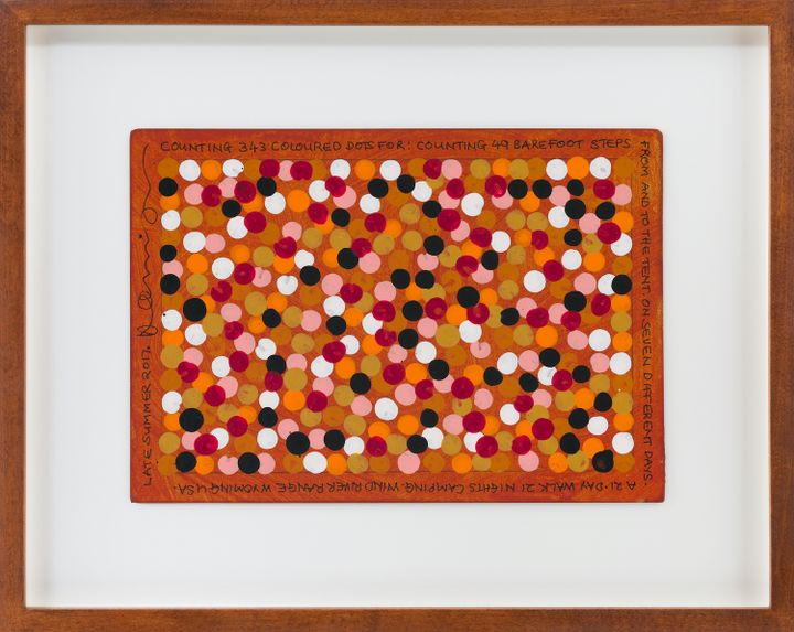 A framed painting on paper features pink, black, and white dots on brown paper.