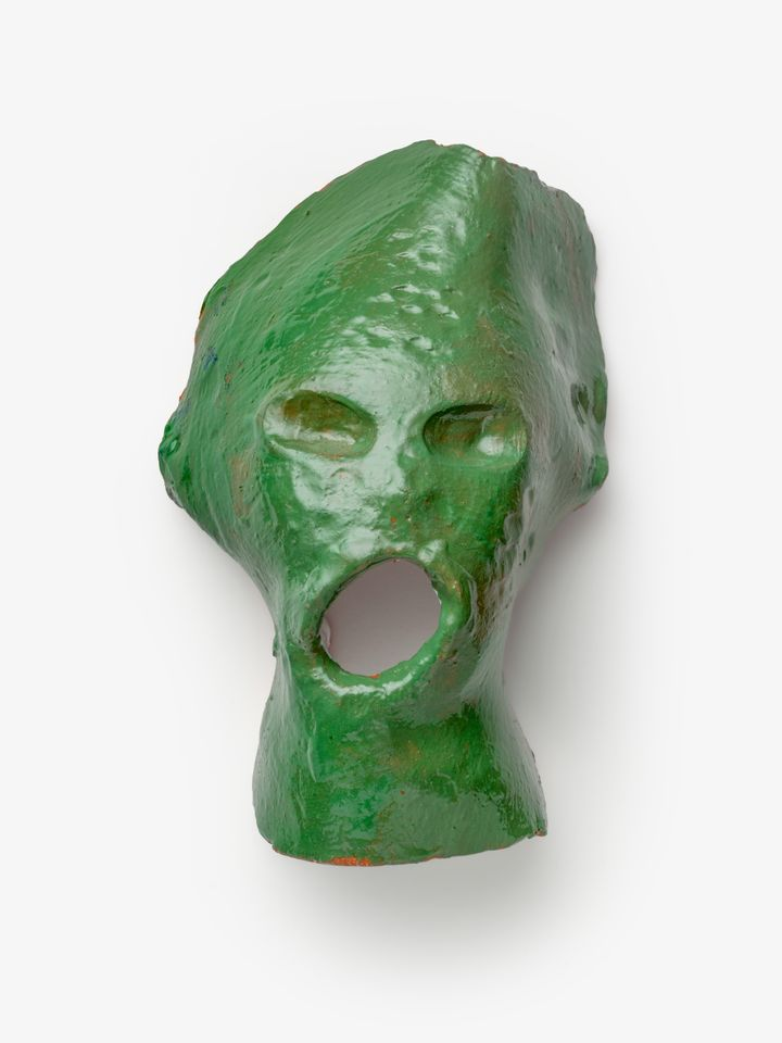 A ghoulish green sculpture features a mouth gaping wide, its surface painted green. It is glazed and therefore appears shiny.