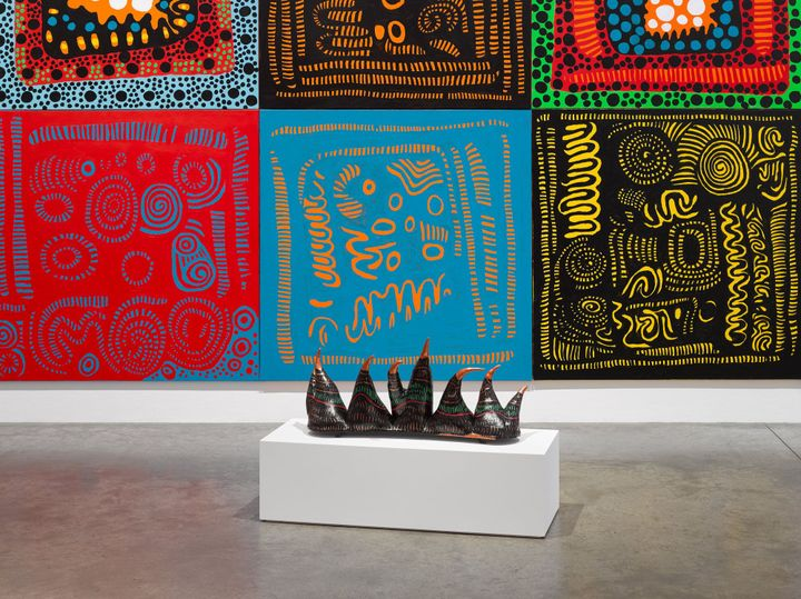 A large abstract painting by Yayoi Kusama is foregrounded by a sculpture made up of a row of spikes. The works are showing in a gallery space.