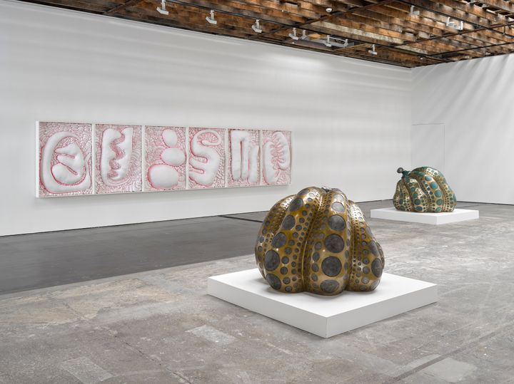 Two pumpkin-shaped sculptures in the gallery space are gold and black, and foreground a pink and white abstract painting running along one of the far walls to the left of the gallery space.