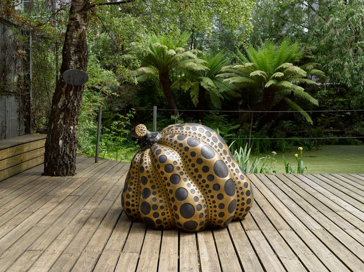A black and gold pumpkin-shaped sculpture by Yayoi Kusama sits on decking outdoors. There is lush green vegetation behind, including a pair of ferns.