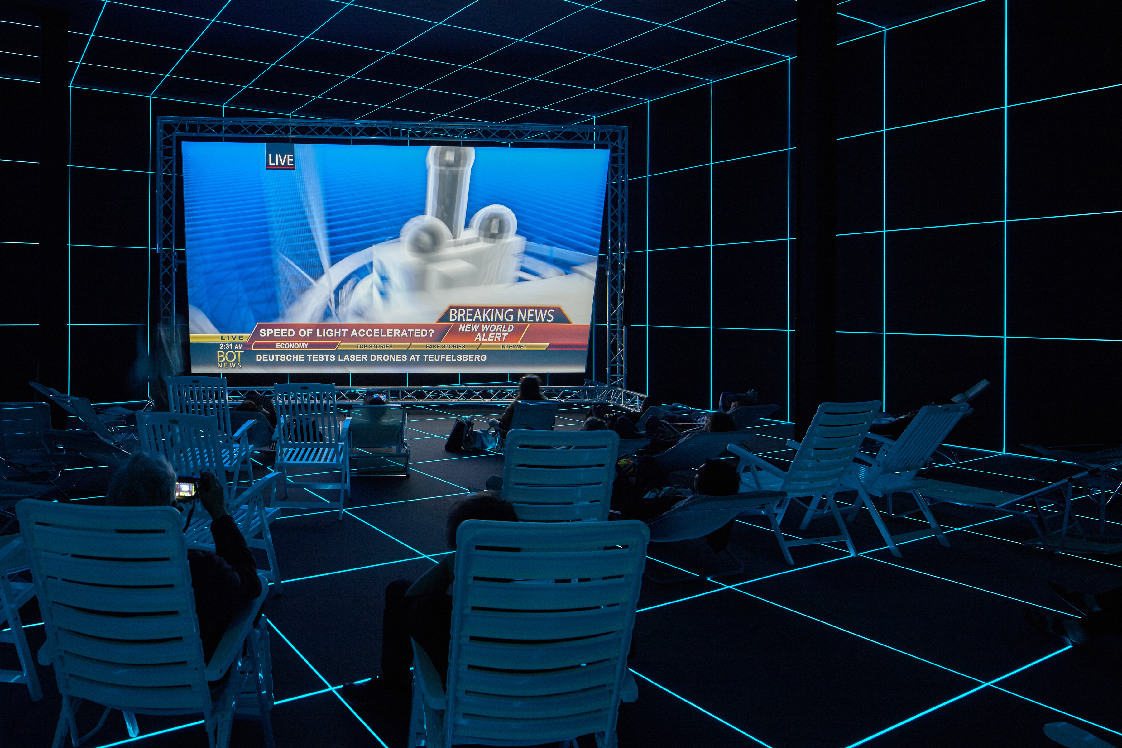 A futuristic looking theatre showing a row of people sitting on lounge seats and facing  big screen showing a single-channel video work by artist Hito Steyerl, entitled Factory of the Sun at the 56th Venice Biennale