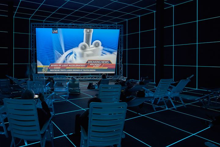 Hito Steyerl, Factory of the Sun (2015). Single channel high definition video, environment, luminescent LE grid, beach chairs. 23 min. Exhibition view: Fabrik, German Pavilion, 56th Venice Biennale, Venice (9 May–22 November 2015). Courtesy the artist, Andrew Kreps Gallery, New York; Esther Schipper, Berlin. Photo: Manuel Reinartz.