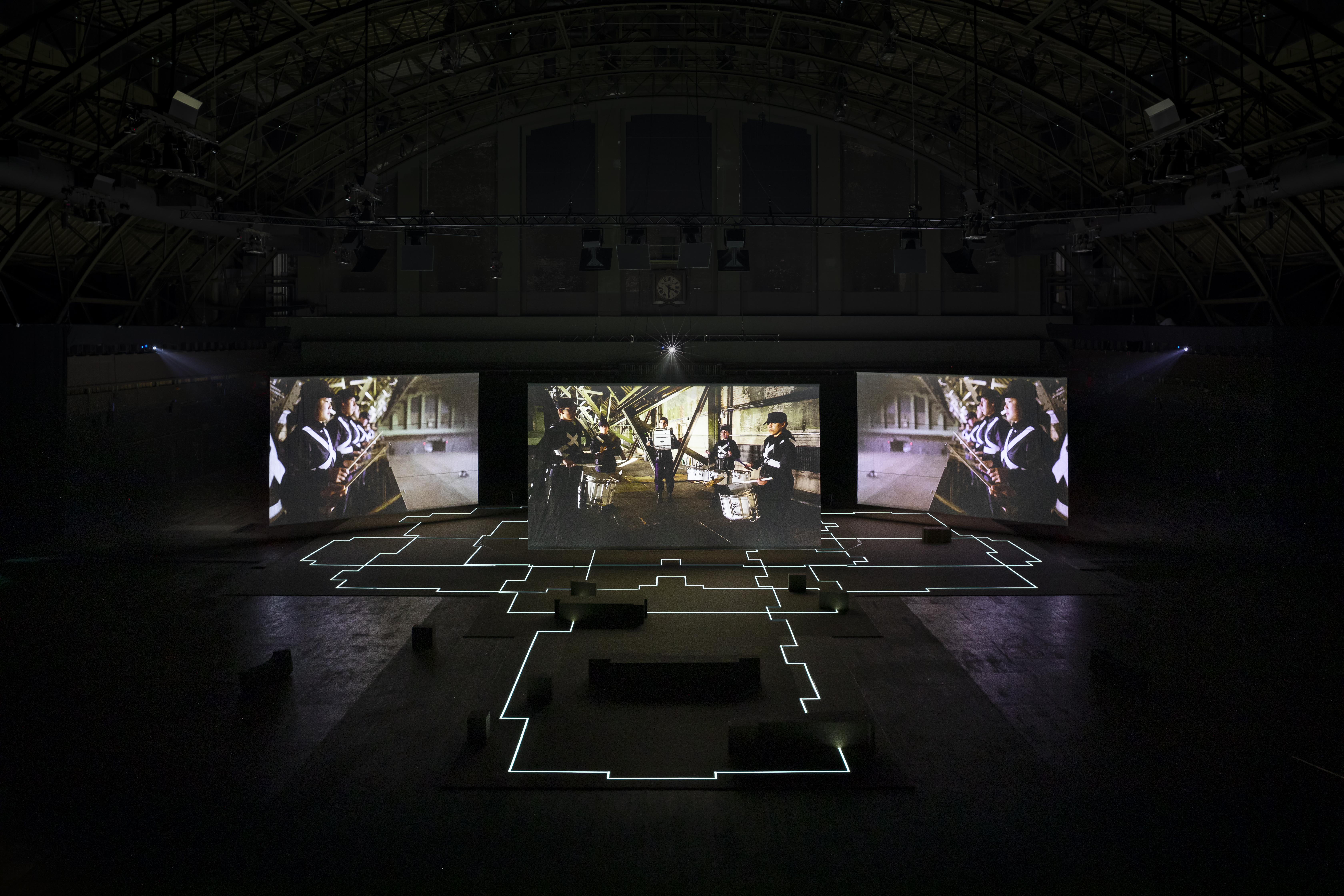 An darken industrial space with three big screens showing a three-channel video work by artist Hito Steyerl at Park Avenue Armory, NYC