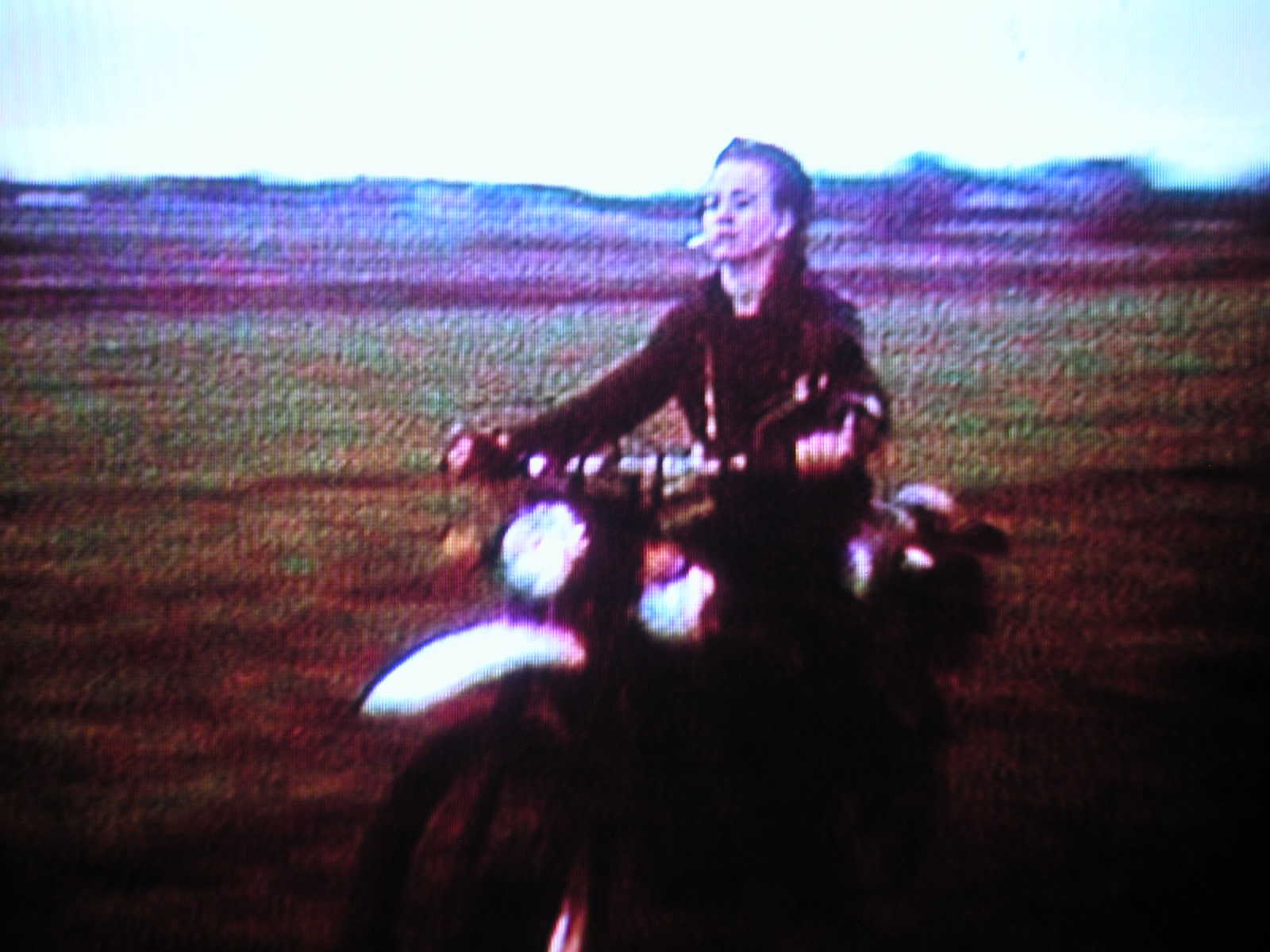 A grainy video still depicting a person riding a motorcycle with a cigarette in their mouth, in a single channel work by Hito Steyerl