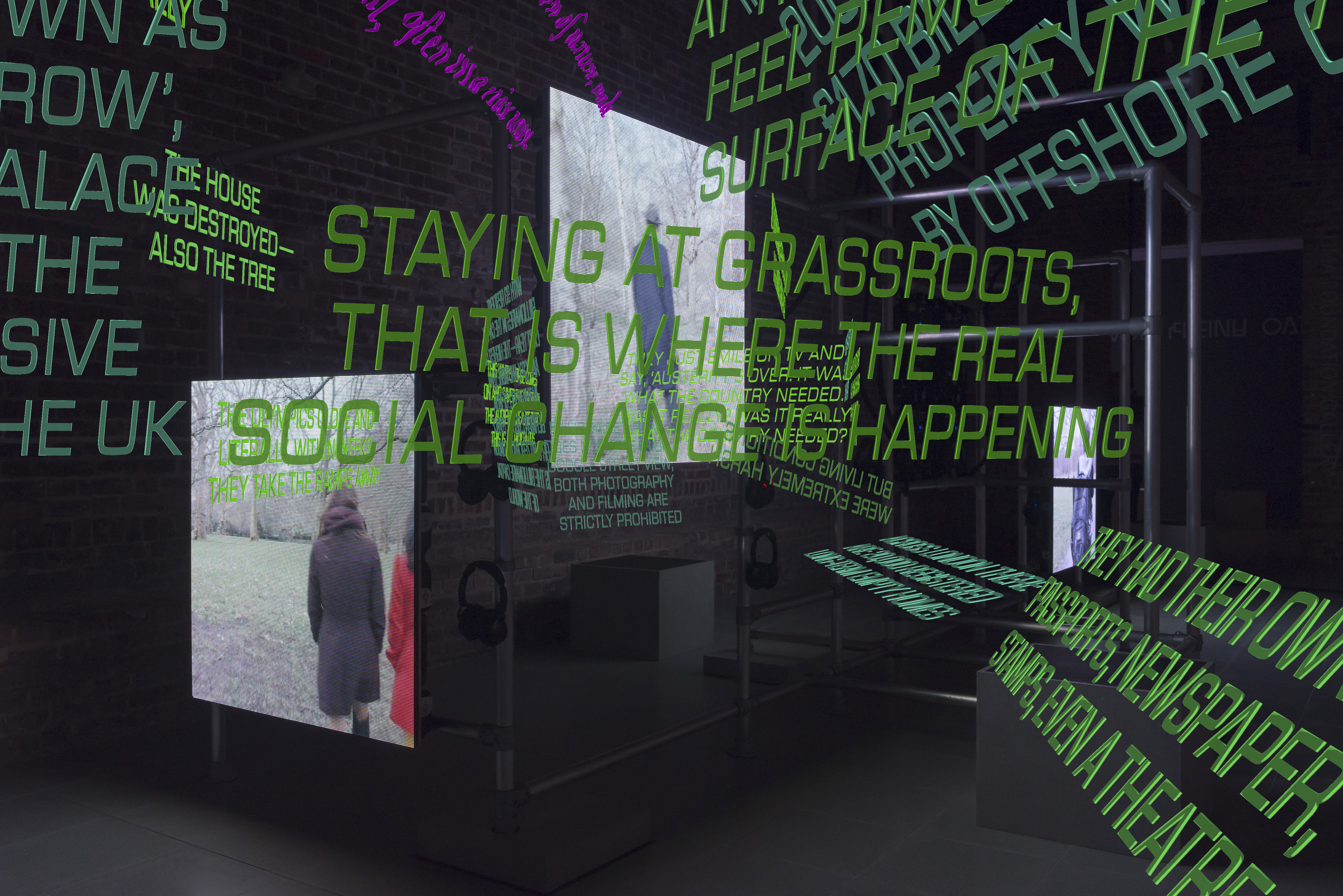 A dark room with big chunk of green texts and flat screens floating around, as a part of artist Hito Steyerls's exhibition at the Serpentine Galleries in London