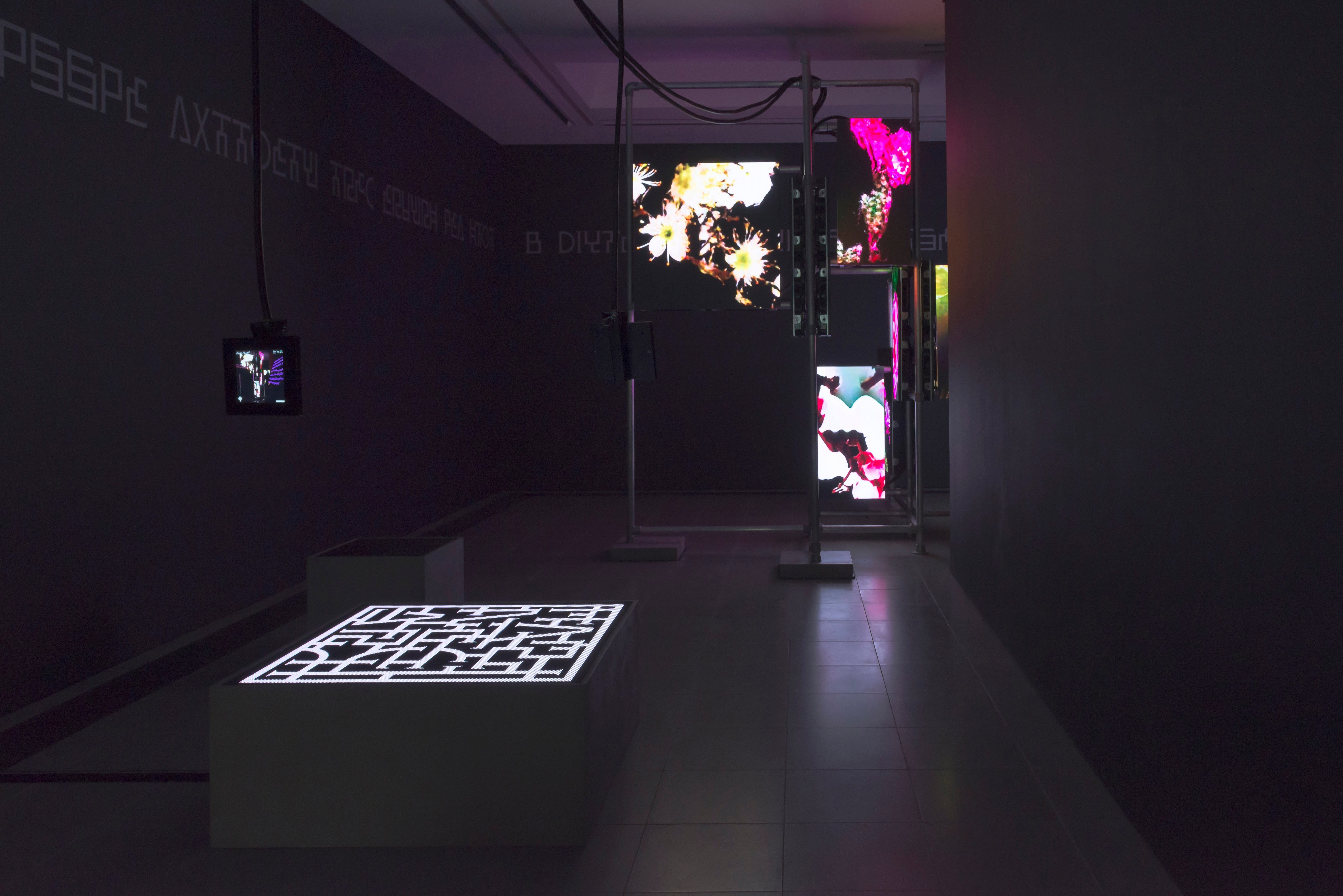 A dark room with multiple screen propped up in metal bars as a part artist Hito Steyerls's exhibition at the Serpentine Galleries in London
