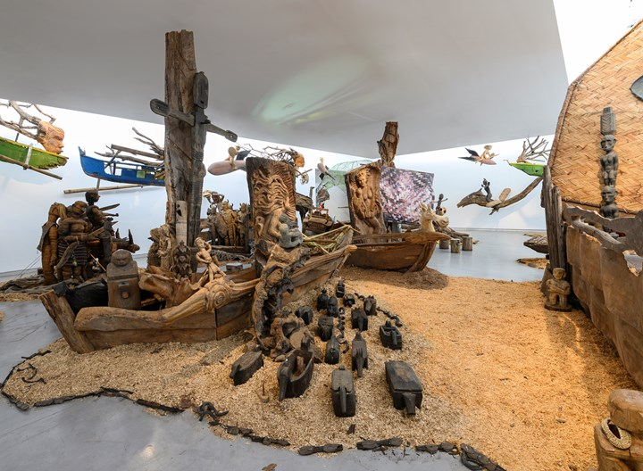 Kidlat Tahimik, Ang Ma-bagyong Sabungan ng 2 Bathala ng Hangin, A Stormy Clash Between 2 Goddesses of the Winds (WW III – the Protracted Kultur War) (2019). Wooden carved icons, ritual objects, interwoven C-print photographs, projected images, audio, mosaic, rattanbasket figurines, back-strap bamboo loom, wrought-iron launch-pads, fibreglass, root sculptures, rotten fishing boats, sawdust, bamboo fences and runo-reed fauna. Dimensions variable. Exhibition view: Leaving the Echo Chamber, Sharjah Biennial 14 (7 March–10 June 2019). Commissioned by Sharjah Art Foundation. Courtesy the artist. Photo: Sharjah Art Foundation