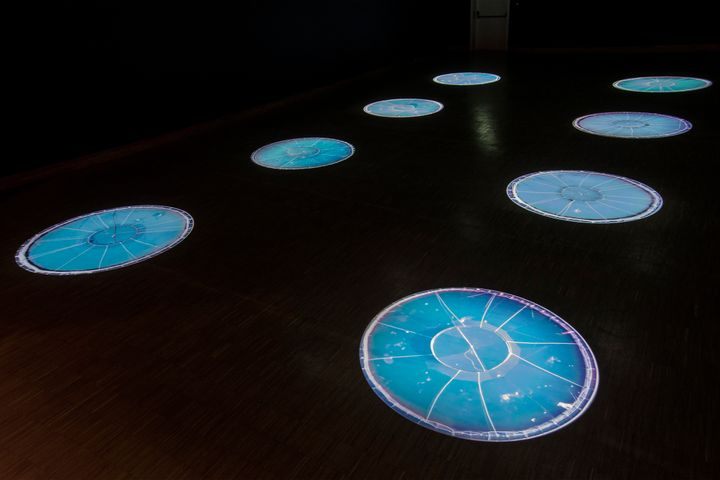 An installation by Cooking Sections features a series of circular structures that resemble fish farms. They are lit up and appear in a darkened gallery space.