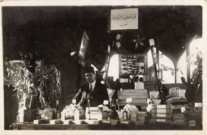 An archival photograph from 1924 shows a man behind a table upon which plants are placed at the Adana Agricultural Fair.