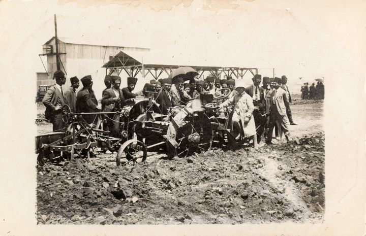 A group of men surround a tractor tilling soil at the Adana Agricultural Fair in 1924.