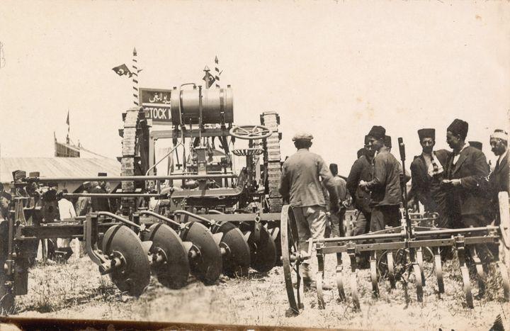 Machines and tractors are photographed alongside a group of men at the 1924 Adana Agricultural Fair.