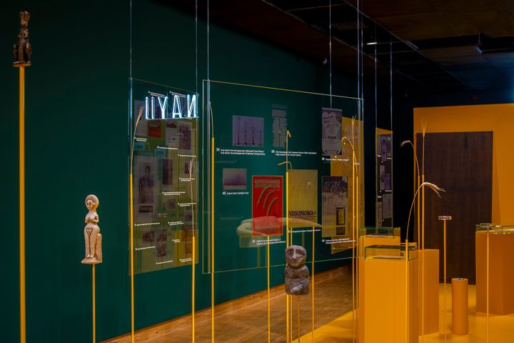 Totemic sculptures are arranged atop yellow structures and between sheets of plexiglass in an installation by Cooking Sections.