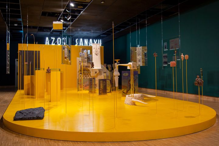A yellow podium features a series of poles and plexiglass sheets that support totemic sculptures and other archival materials in an installation by Cooking Sections.