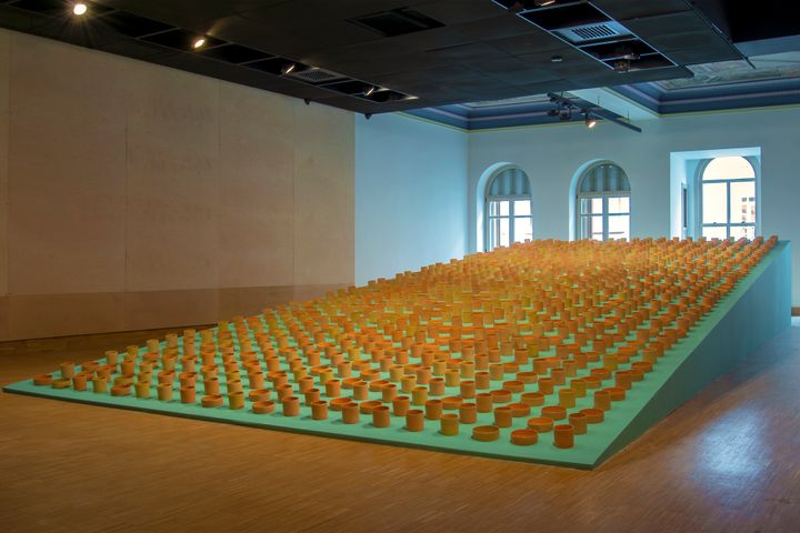 A series of light brown vessels of varying heights are placed on a light-blue surface as part of an installation by Cooking Sections.