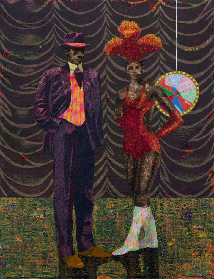 A man and woman stand on a stage. The man is in a purple suit and bowler hat, while the woman is in an orange bodice with feathers on her head.
