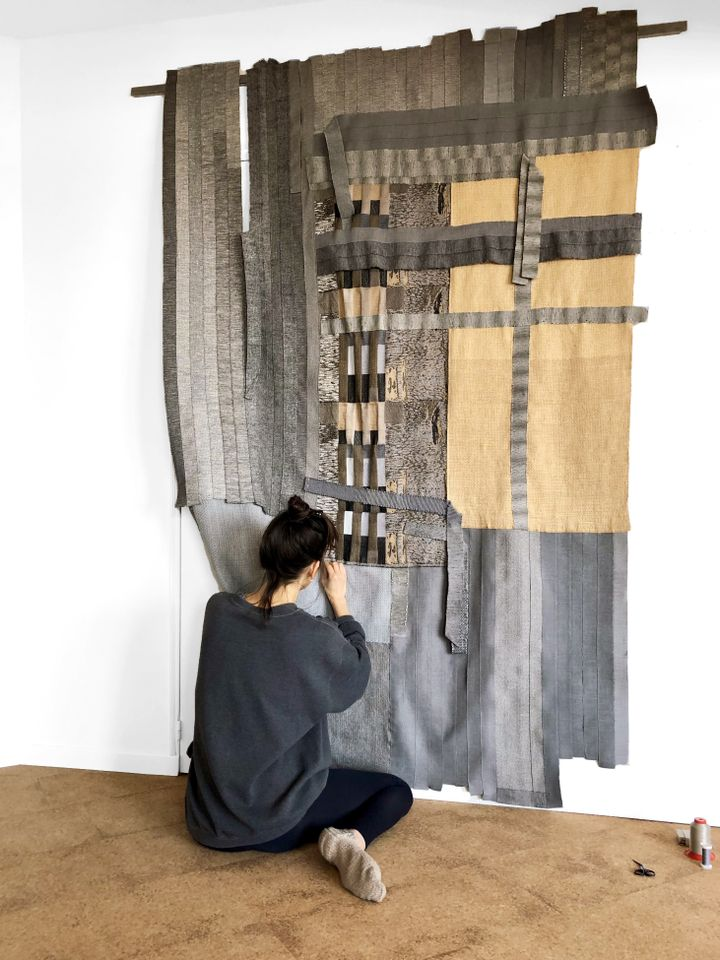 The artist Hana Miletić is pictured sitting on the ground, working on a large textile piece made up of different, woven parts.