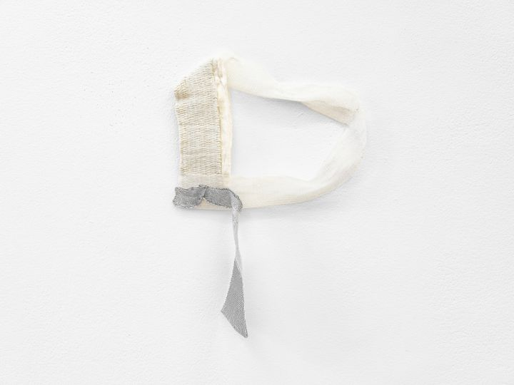 A fragmentary, subtle textile work by Hana Miletić in shades of grey and white hangs against a white wall.