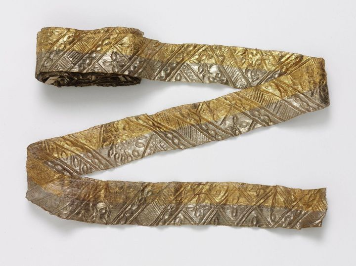A pattern, silver gilded ribbon belonging to the Victoria & Albert Collection is photographed against a grey background.