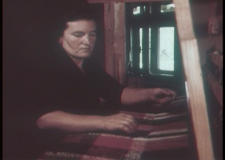 A grainy image of a woman captures her working at a loom.