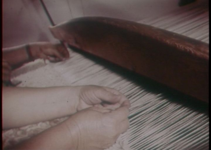 A grainy image captures the hands of women working a loom.