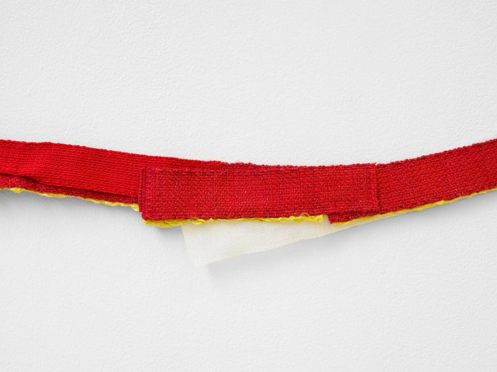 A close-up shot of a textile work by Hana Miletić features a strip of red textile hanging against a white wall.