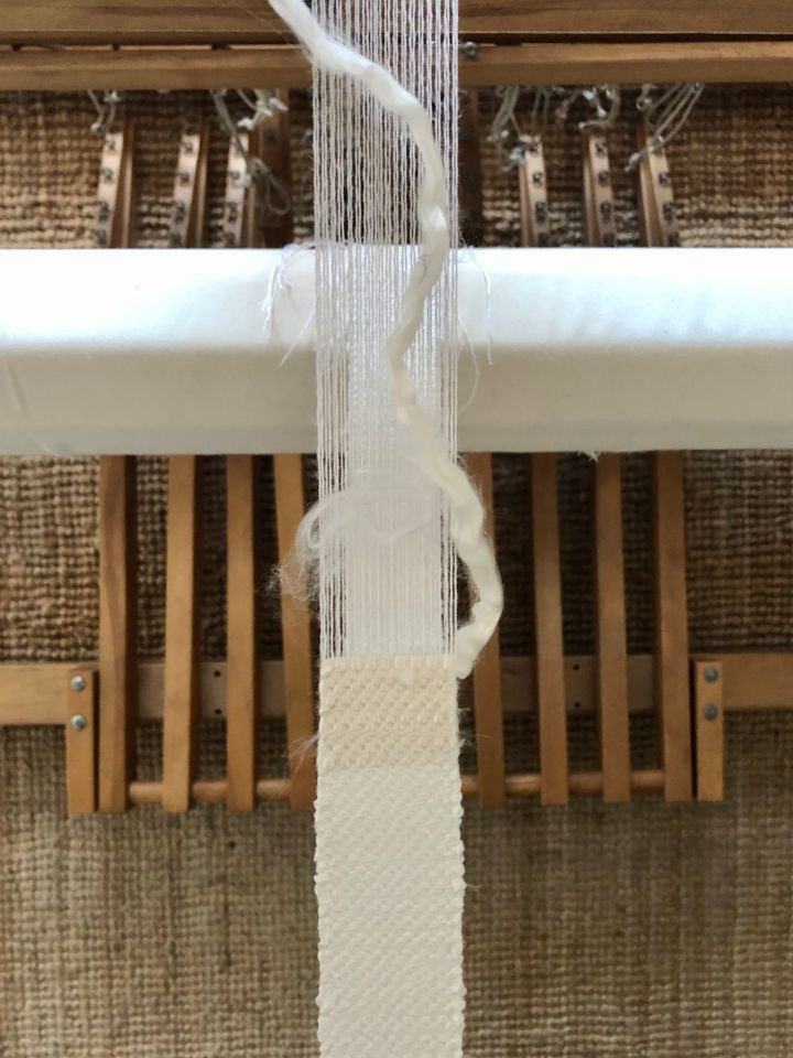 A close-up photograph of thread being woven on the loom.