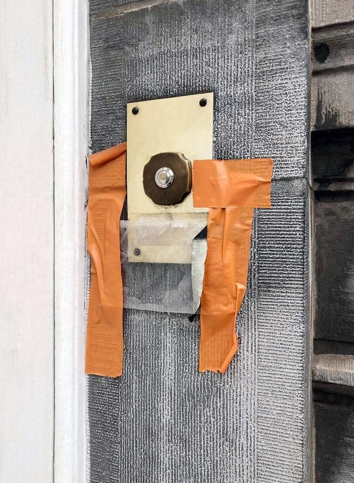 Orange tape surrounds a doorbell. The image inspired the creation of Hana Miletić's orange, fragmentary textile work.
