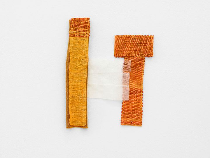 A fragmentary orange textile piece by Hana Miletić is photographed hanging on the wall.