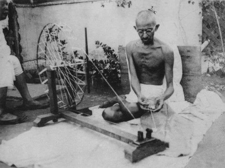 A black and white photograph captures Gandhi sitting on the floor, weaving.