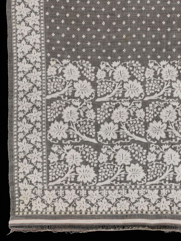 A segment of fine muslin cloth with repeated floral patterns on it in white is photographed up close.