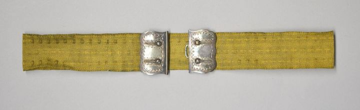 A gold silk belt with a metal buckle from the early 20th century, belonging to the Victoria & Albert Collection, is photographed against a grey background.