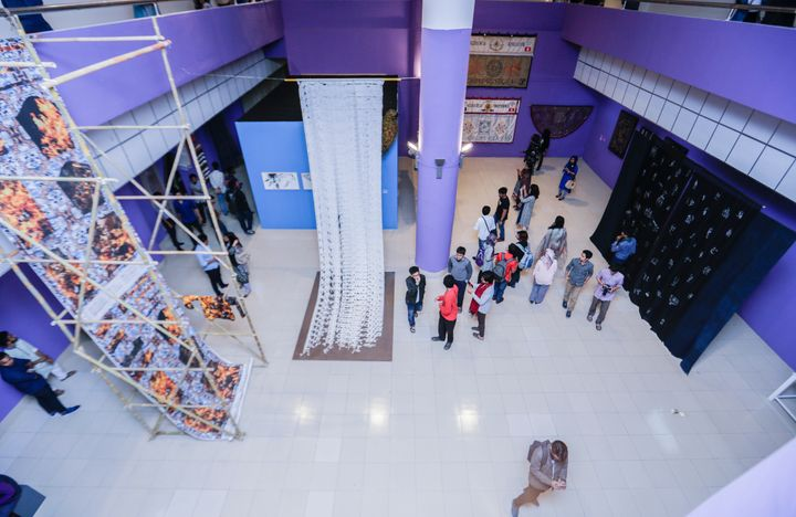 An aerial shot of textile works showing at the Dhaka Art Summit of 2018, in a gallery space with purple walls.