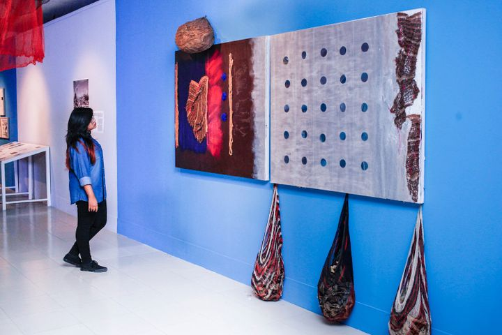 A textile work with teardrop-shaped hanging parts is placed against a blue wall, showing at the Dhaka Art Summit of 2018.