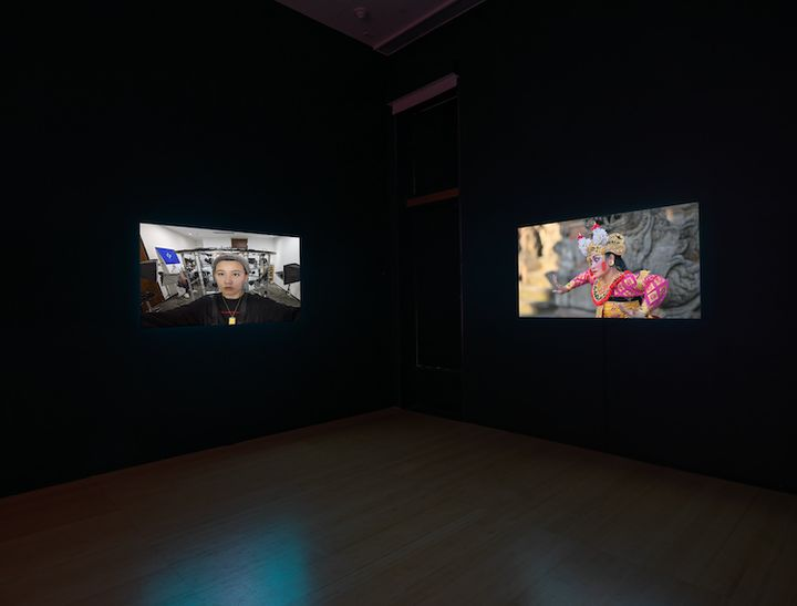 Two screens in a darkened gallery space show the artist Lu Yang to the left, while the right-hand screen shows a Balinese traditional dancer.