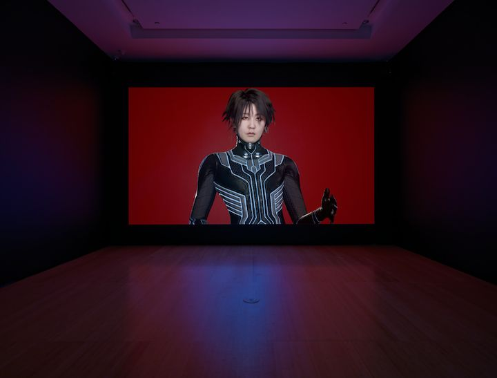 One large screen in a darkened gallery space features the artist Lu Yang dressed as her alter ego Doku in futuristic clothing, against a red background.