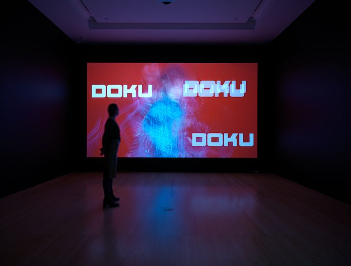 A large screen in a darkened gallery space features the word 'Doku' written three times against a red background.