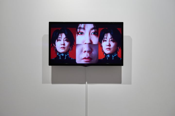A screen in the gallery space is split in four, showing different angles of the artist Lu Yang's face.