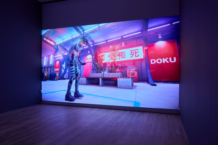 A large screen in the gallery space shows the artist Lu Yang as her alter ego Doku in a futuristic setting.